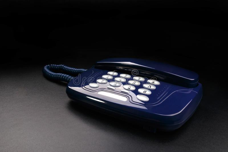 Outdated telephone with push buttons on black background stock photography