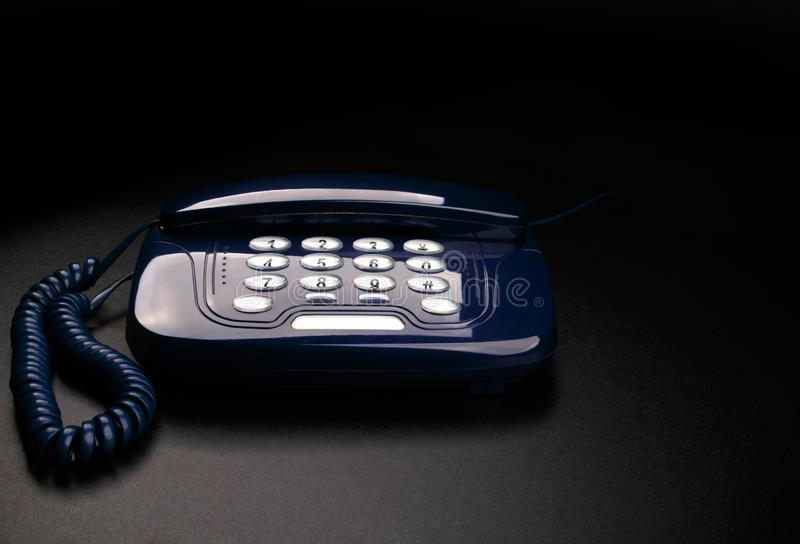 Outdated telephone with push buttons on black background royalty free stock image