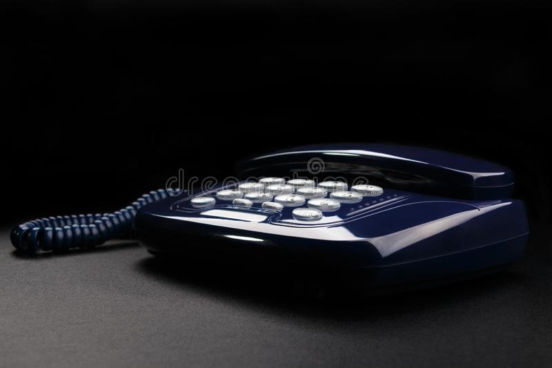 Outdated telephone with push buttons on black background stock photos