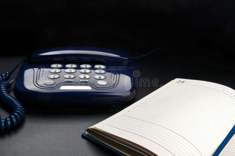Outdated telephone with push buttons and personal organizer on black background royalty free stock images