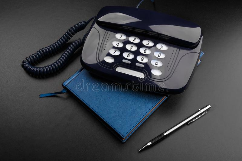 Outdated telephone with push buttons standing on personal organizer. Black background. Outdated stationary dark blue telephone with push buttons standing on royalty free stock photography