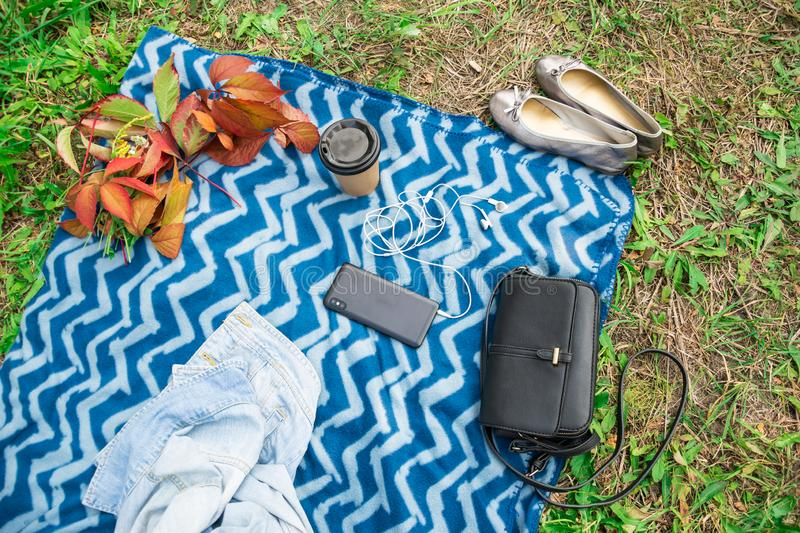 Outdoor activities on a blue plaid with a mobile phone headphones and coffee stock image