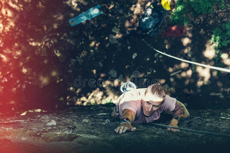 Outdoor Activity Man. Extreme Rock Climbing Lifestyle. Male Rock Climber On A Cliff Wall. Climber on a steep section on the rock royalty free stock image
