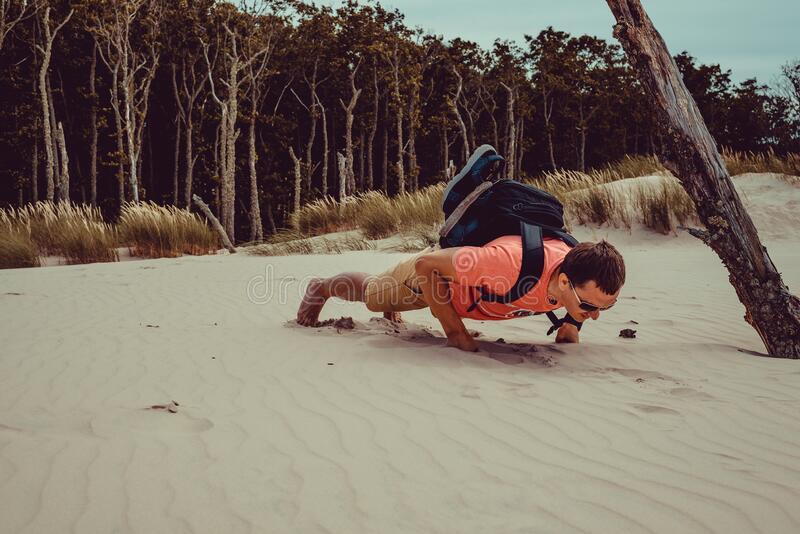 Outdoor Adventure. Traveler with backpack do push ups. Man has fun journey. Freedom travel. Backpacker holiday. Active healthy. Lifestyle concept. Poland Europe stock photos