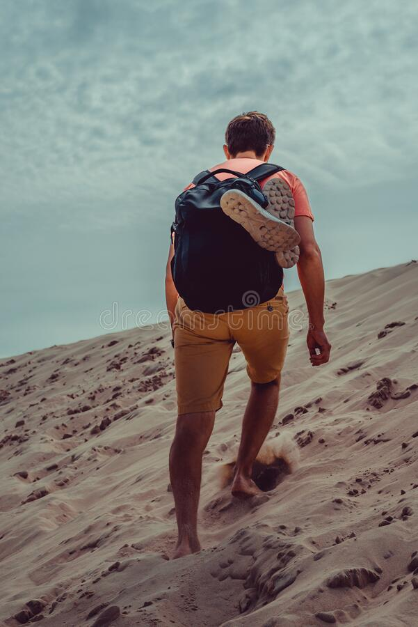 Outdoor Adventure. Traveler with backpack explore world. Man climbing up dune. Freedom travel. Backpacker holiday. Active. Lifestyle. Poland Europe vacation stock photography