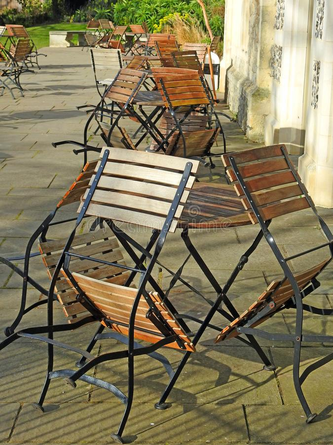Outdoor alfresco dining chairs seats in stack row patio cafe restaurant stock image