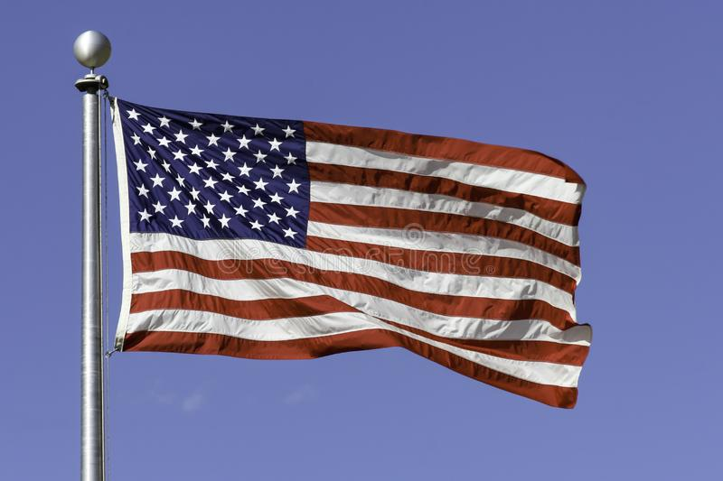 Outdoor American Flag flying with a blue sky in the background. Outdoor United States of American 50 Stars and red white stripes Flag flying with a blue sky in stock image