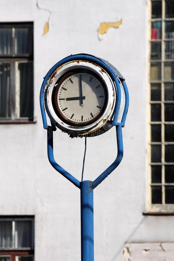 Outdoor analog clock with rusted metal frame in middle of abandoned industrial complex with old dilapidated building in background stock photos