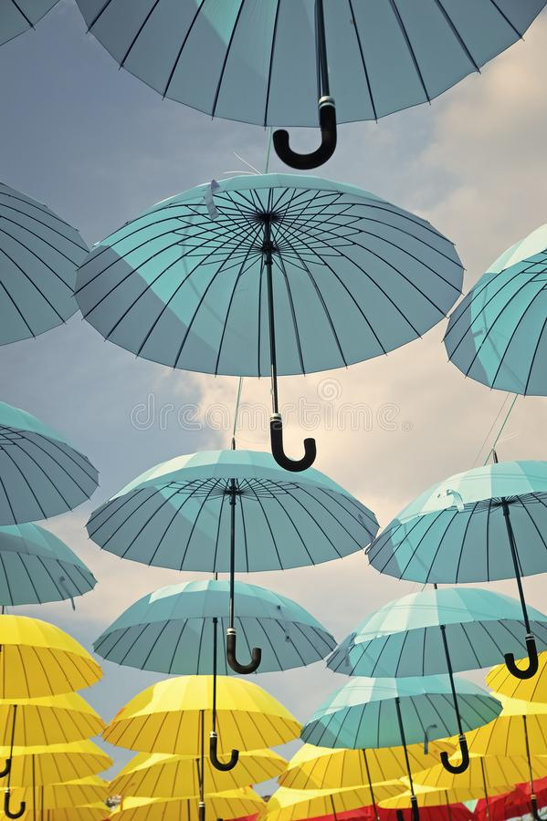Outdoor art design and decor. Umbrellas float in sky on sunny day. Umbrella sky project installation. Holiday and royalty free stock photography