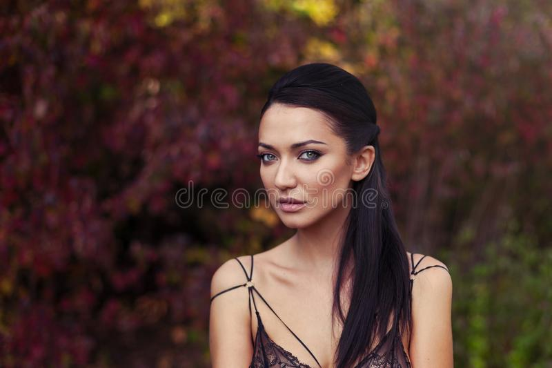 Outdoor atmospheric lifestyle photo of young beautiful lady. Black hair andgreen eyes. Warm autumn. Warm spring royalty free stock image
