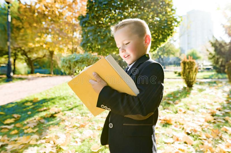 Outdoor autumn portrait of schoolboy reading book, background of yellow trees in the park, boy in jacket, golden hour. Back to school stock images