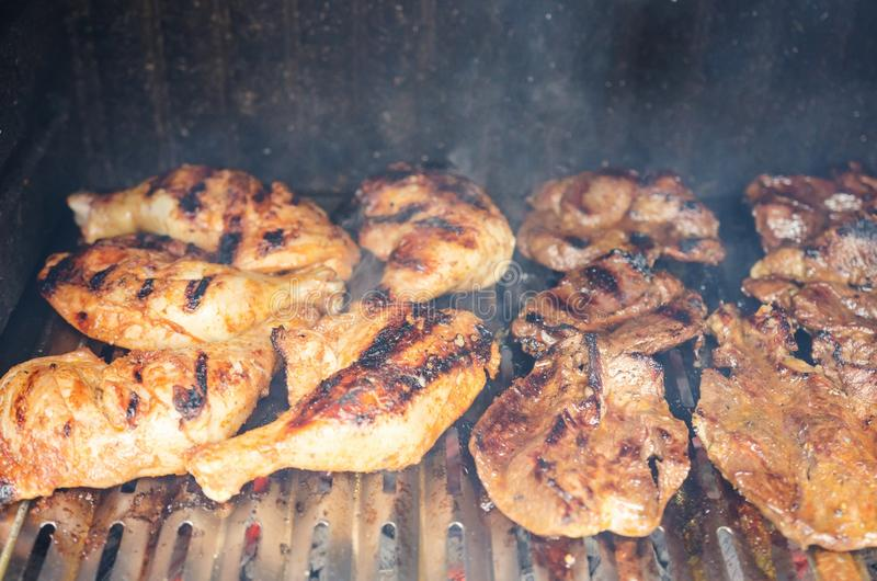 Outdoor barbecue -grilling chicken and beef meat. Closeup of outdoor barbecue, grilling chicken, beef and pork meat over fire, burned stripes visible, smoke and stock photos