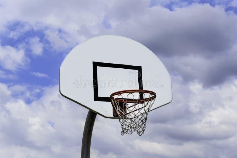 Outdoor Basketball Goal against Blue Blue Sky and White Clouds. An Outdoor Basketball Goal against a Blue Blue Sky with White Clouds royalty free stock photo
