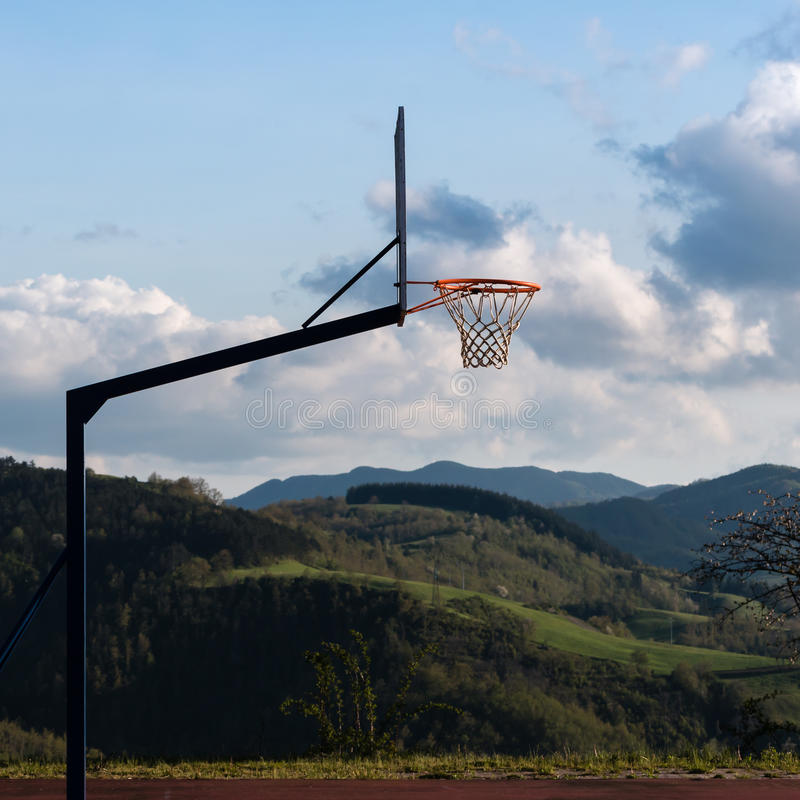 Outdoor Basketball Hoop in Court. Little Hill and Cloudy Sky in Background stock photo