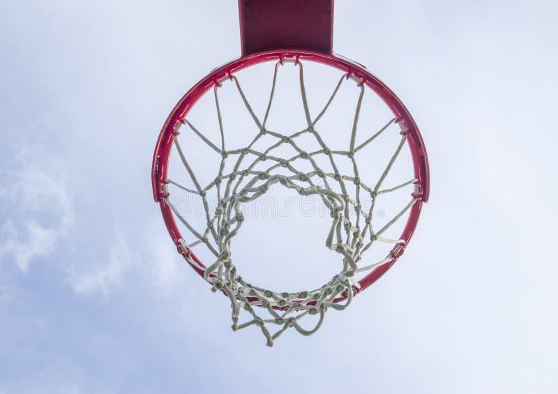 An outdoor basketball hoop set against blue sky. An outdoor basketball hoop set against cloudy blue sky royalty free stock photos