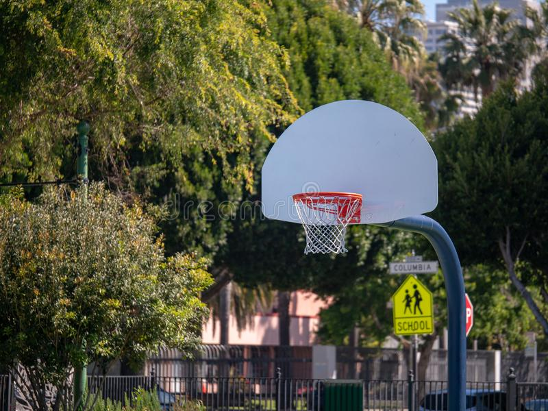Outdoor basketball hoop sitting on a court in a school zone play. An outdoor basketball hoop sitting on a court in a school zone playground royalty free stock image