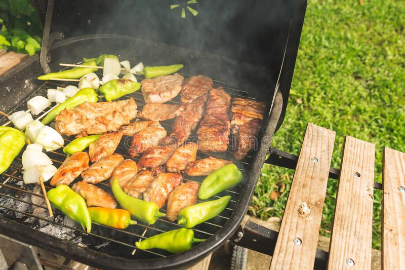 Outdoor bbq party steak grill on sunday weekend. Outdoor bbq party steak grill on sunday weekend with smoke hot cooking royalty free stock photo