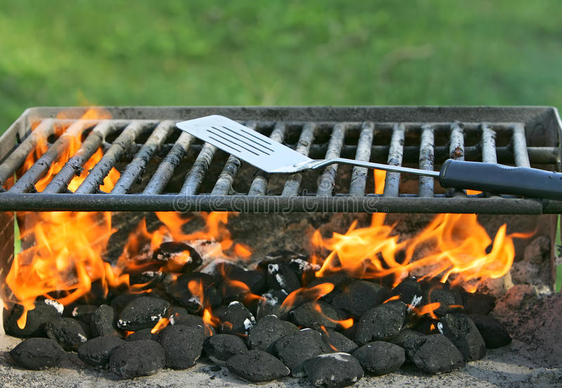 Outdoor bbq pit. Charcoal on fire heating up a barbecue pit before cooking royalty free stock photo