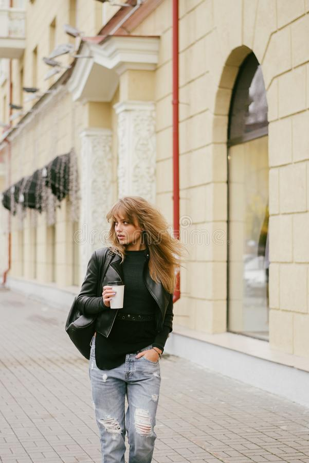 Portrait of a beautiful girl on the street, holding a paper cup stock images