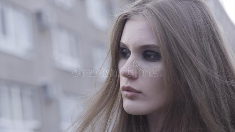Outdoor beauty portrait of young brown haired girl looking aside over blurred city line background. Action. Close up for royalty free stock photo