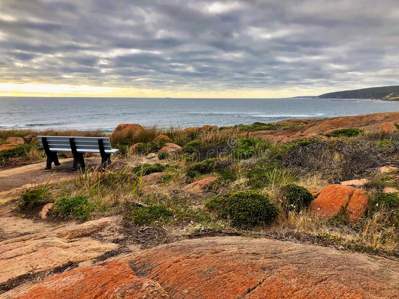 Outdoor bench on rocky coastal area at Cape Leeuwin during evening, Western Australia. Outdoor bench on rocky coastal area at Cape Leeuwin during evening at royalty free stock photography