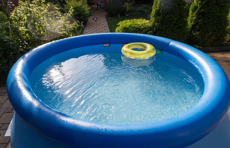 Outdoor blue inflatable pool with water stock photography