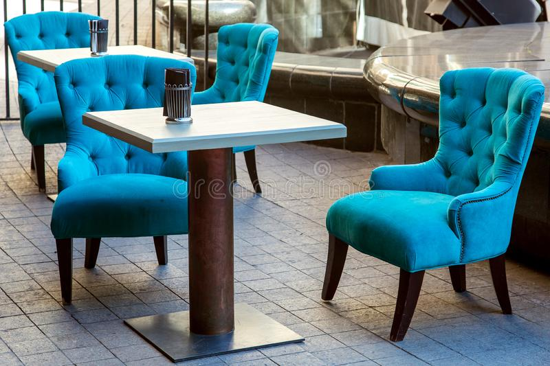 An outdoor cafe with square wooden tables. An outdoor cafe with square wooden tables and an iron leg and upholstered armchairs with high backs and sheathed with royalty free stock image