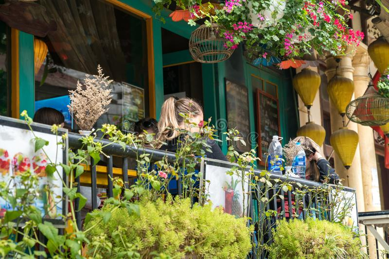 Outdoor cafe with a woman having drink. The cafe decorated with a lot of plant and flower.  stock photography