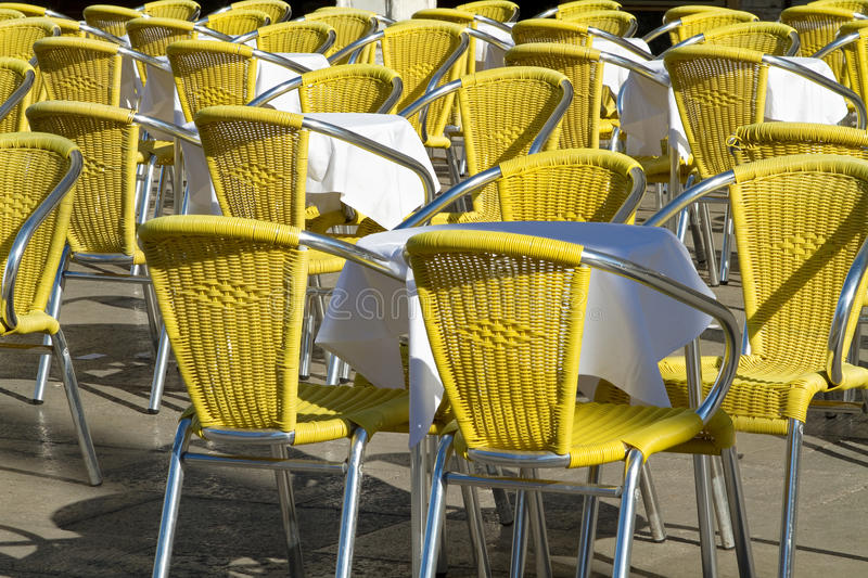 Outdoor cafe with yellow chairs.