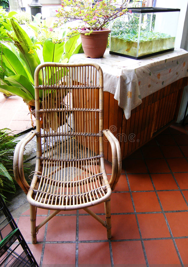 Outdoor cane furniture. A picture of a cane or rattan comfortable and relaxing chair suitable for use on the patio, porch, balcony, etc. Design with casual stock images
