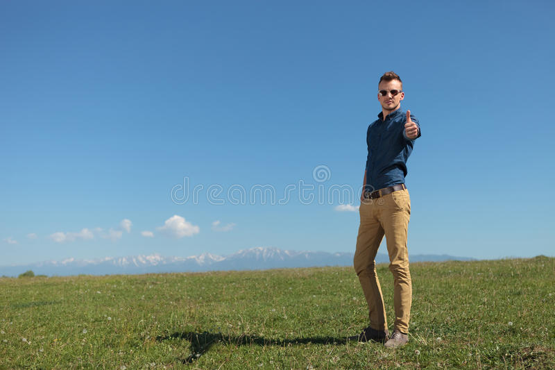 Outdoor casual man shows thums up. Casual young man standing outdoor on a green field of grass and showing the thumb up sign to the camera stock photography