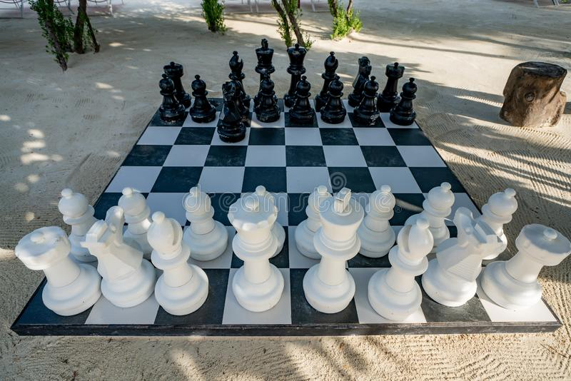 Outdoor Chess Game at Big Chequer Board. Super big size of black and white chess game pieces.  stock photos