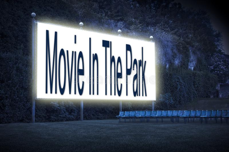 Outdoor cinema with chairs and white projection screen with `Movie In The Park` text written on it.  stock photos