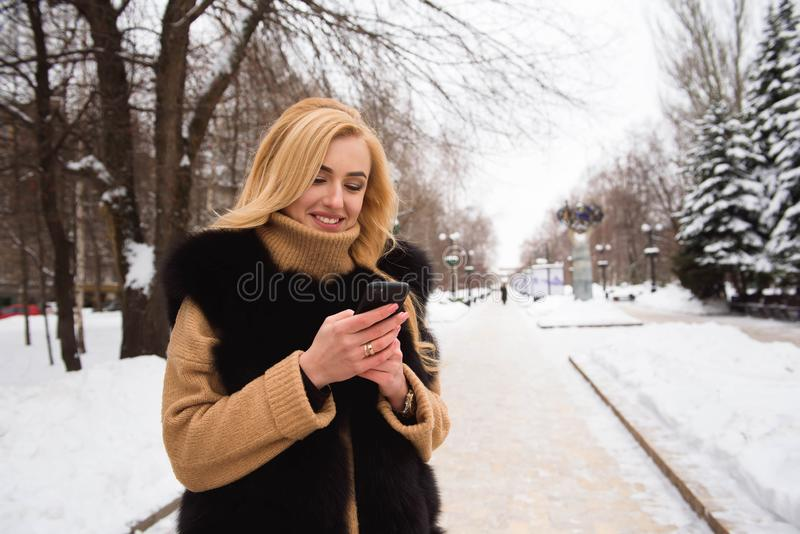 Outdoor close up photo of young beautiful happy smiling girl walking on street in winter royalty free stock photography