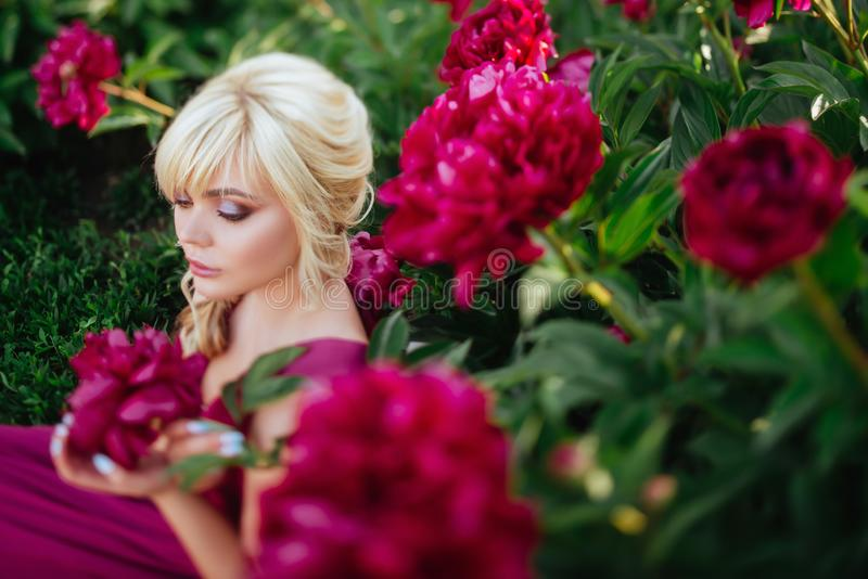 Outdoor close up portrait of beautiful young woman in the blooming garden. Female spring fashion concept stock images