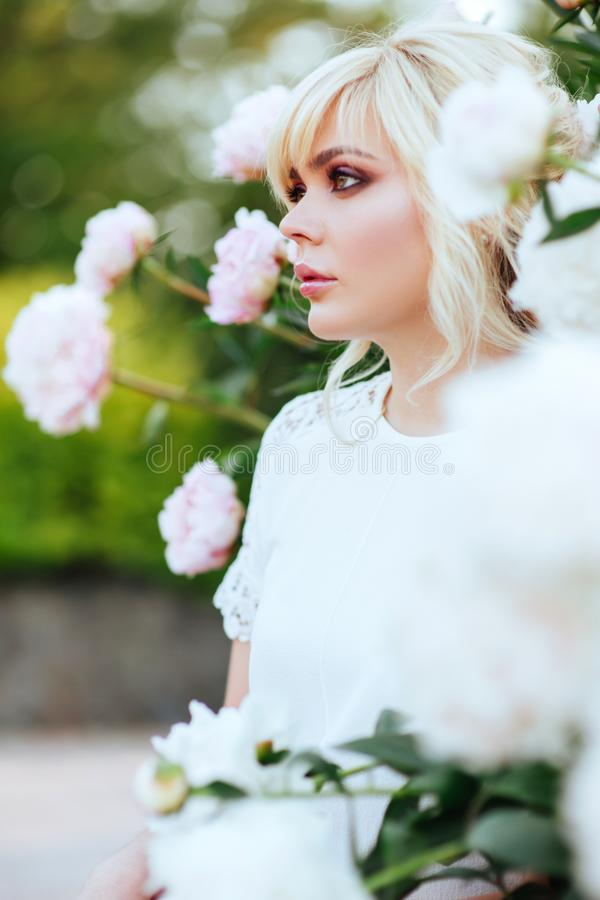Outdoor close up portrait of beautiful young woman in the blooming garden. Female spring fashion concept stock photos