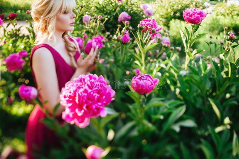 Outdoor close up portrait of beautiful young woman in the blooming garden. Female spring fashion concept. Outdoor close up portrait of beautiful young woman with royalty free stock image