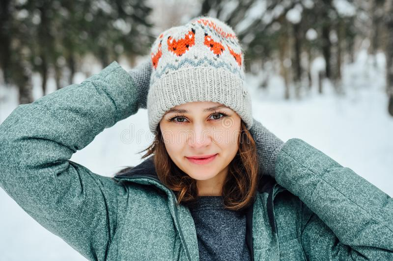 Outdoor close up portrait of young beautiful happy girl, wearing stylish knitted winter hat. royalty free stock image