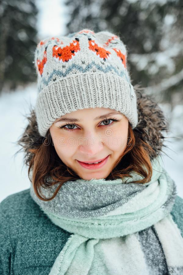 Outdoor close up portrait of young beautiful happy girl, wearing stylish knitted winter hat. Model expressing joy and looking at camera. Day light royalty free stock photography