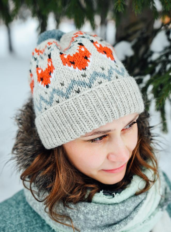 Outdoor close up portrait of young beautiful happy girl, wearing stylish knitted winter hat. Model expressing joy and looking at camera. Day light royalty free stock image