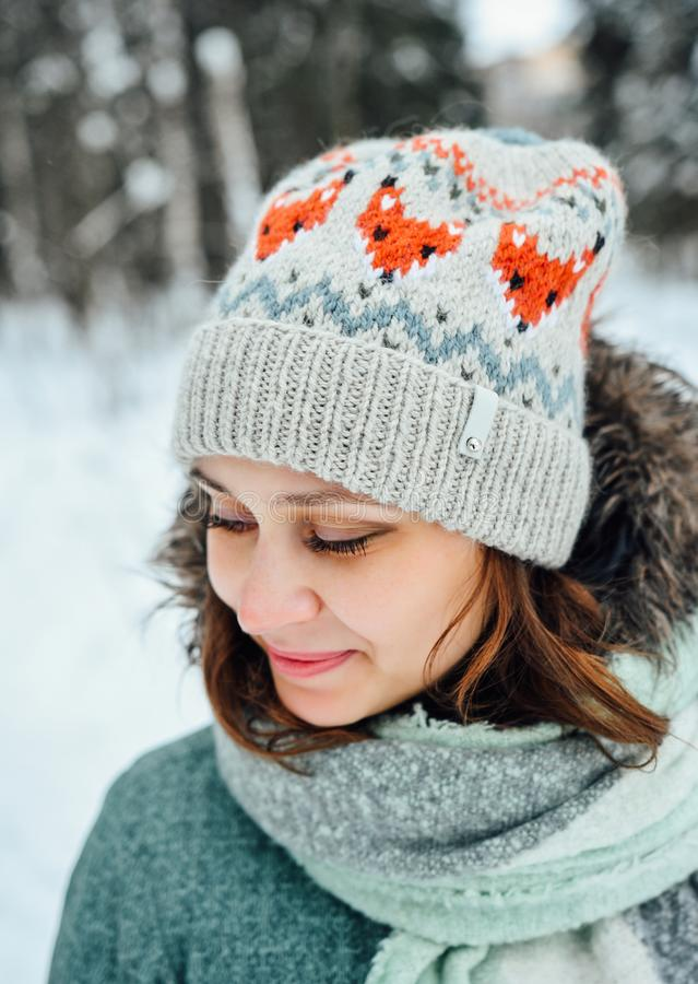Outdoor close up portrait of young beautiful happy girl, wearing stylish knitted winter hat. Model expressing joy and looking at camera. Day light royalty free stock images