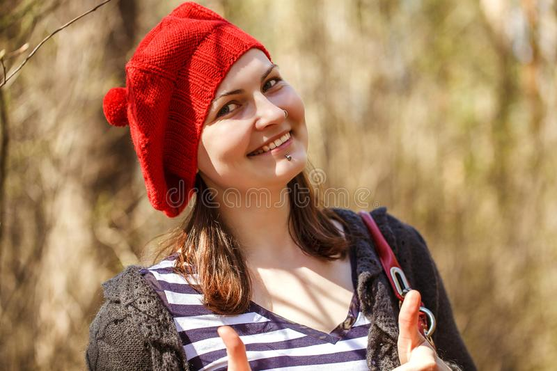 Outdoor close up portrait of young beautiful happy smiling girl wearing french style red knitted beret stock photo