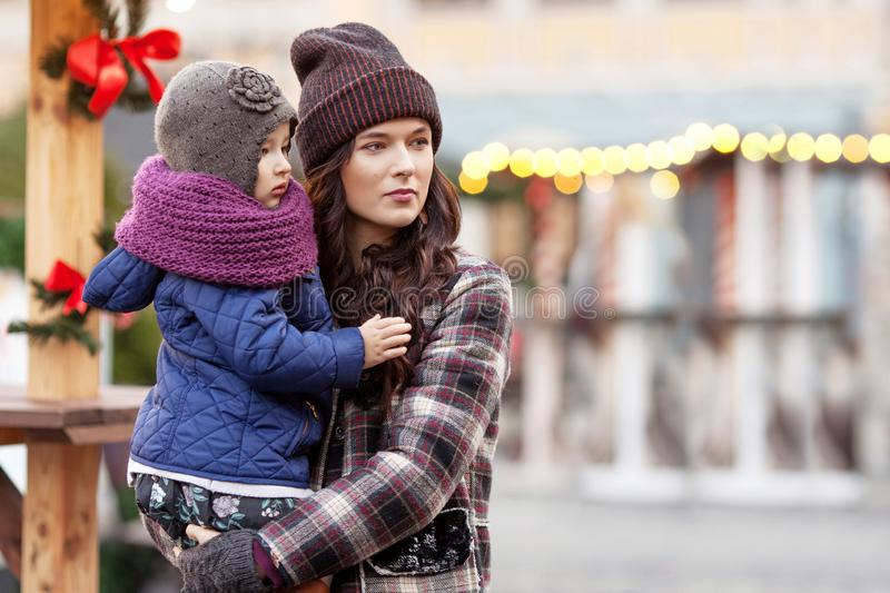 Outdoor close up portrait of young woman and little girl in Christmas decorations on street of  city. Happy family with little royalty free stock photography