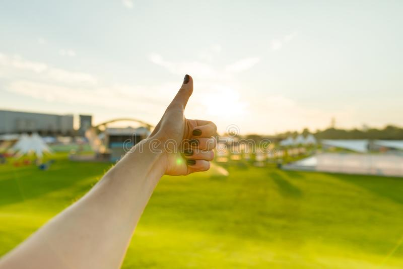 Outdoor closeup woman`s hand showing thumb up, positive sign symbol gesture ok royalty free stock image
