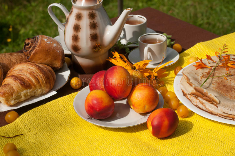 An outdoor composition with tea cups, a tea pot, a plate of pancakes, pastry, ripe fruit and field flowers on a bright table cloth. An outdoor composition with royalty free stock photography