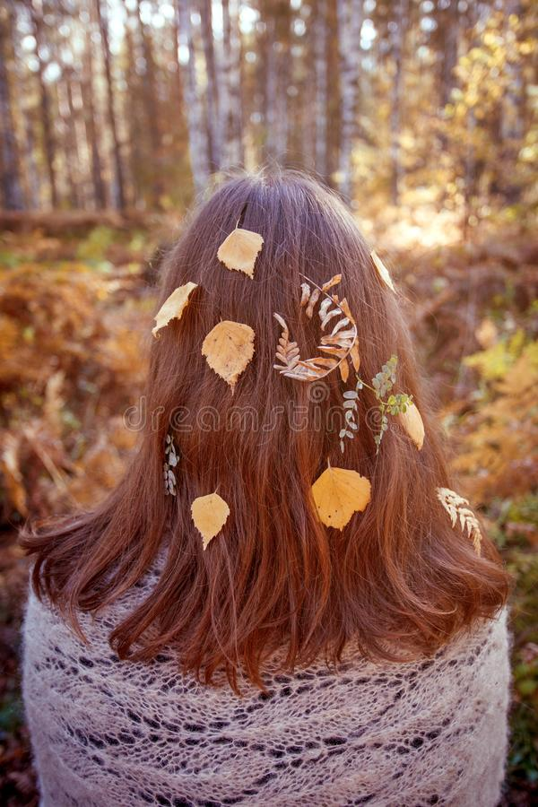 Outdoor conceptual photo of young beautiful lady. Brown hair with autumn fall leaves. Warm autumn, seasonal hair care stock photo
