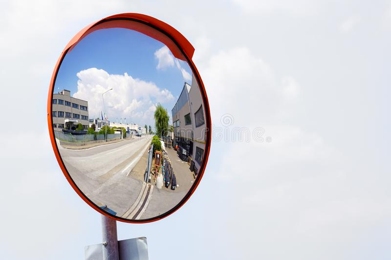 Outdoor convex safety mirror hanging on wall with reflection of an urban roadside view of cars parked along the street stock image