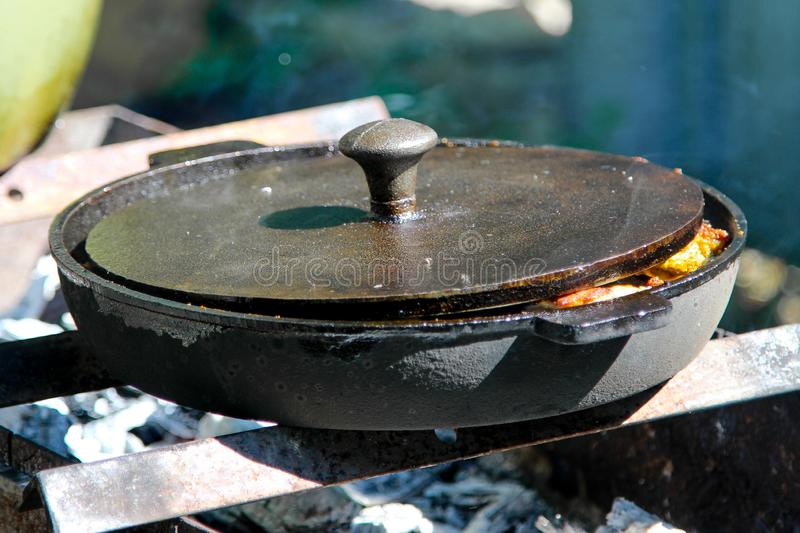 An outdoor cooking with cast iron frying pan royalty free stock photography