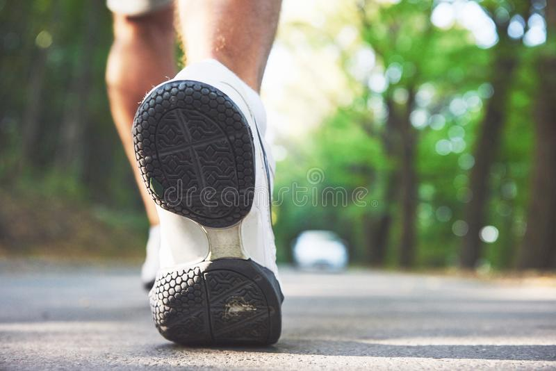 Outdoor cross-country running in concept for exercising, fitness and healthy lifestyle. Close up of feet of young runner royalty free stock photography