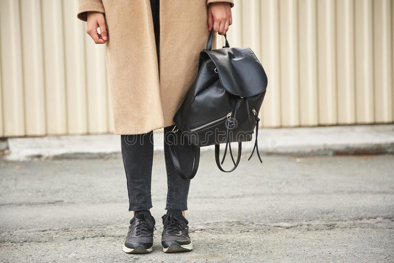 A girl in a brown cashmere coat with a black backpack. Stylish modern girl. royalty free stock photo